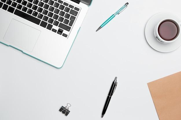 Tavolo scrivania da ufficio con computer, forniture, fiori e tazza di caffè