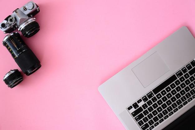 Tavolo scrivania da ufficio con laptop, macchina fotografica e caffè lenti.