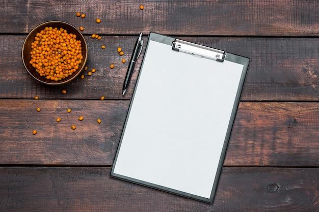 Tavolo scrivania da ufficio con quaderni e bacche fresche di olivello spinoso sulla tavola di legno