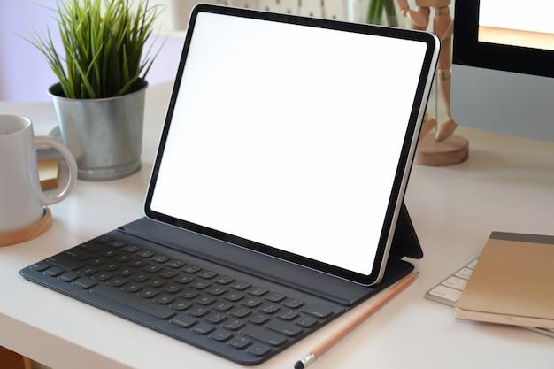 Tavolo scrivania da ufficio con tablet schermo vuoto, tastiera del computer e altri articoli per ufficio
