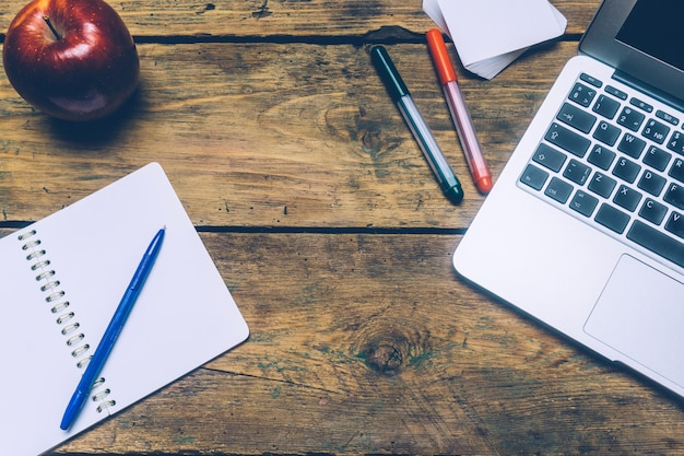 Tavolo scrivania da ufficio con un computer portatile, penne, un quaderno e una mela.