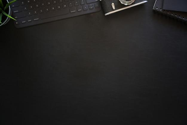 Tavolo scrivania da ufficio in pelle scura con tastiera tablet e macchina fotografica d'epoca