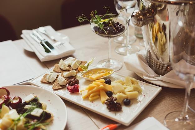 Tavolo servito con antipasti, posate, bicchieri e sputacchiera per degustazione di vini.
