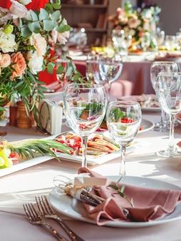 Tavolo servito per banchetti di nozze con posate e fiori in vaso.