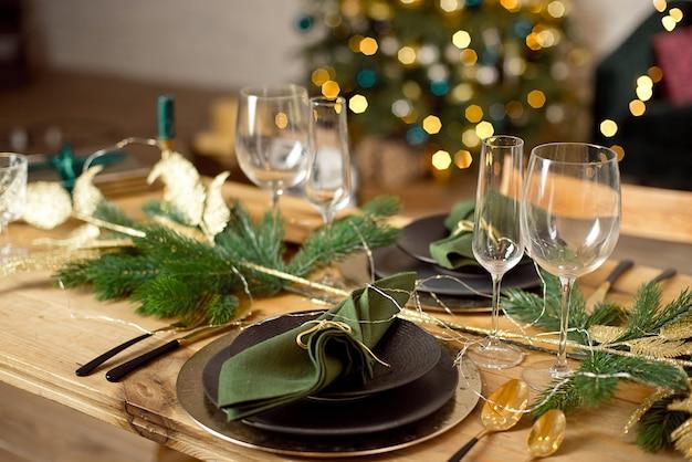Tavolo servito per la cena di natale in soggiorno, vista ravvicinata, impostazione della tavola, decorazioni natalizie.