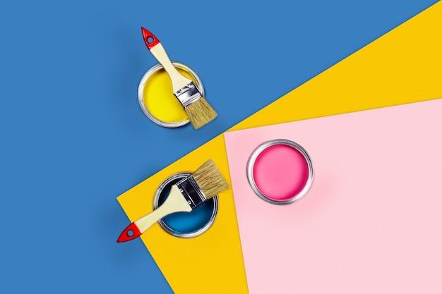 Tavolo tricolore con vasetti di vernice e pennelli.