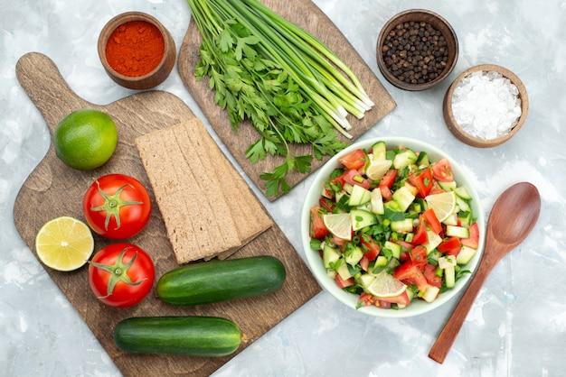 Tavolo vista dall'alto con verdure come pomodori cetrioli e insieme con patatine limoni e verdure su bianco, insalata di verdure