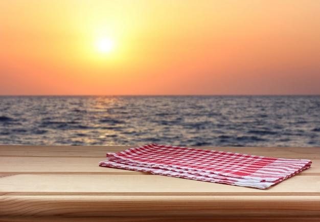 Tavolo vuoto con un asciugamano rosso contro il tramonto sul mare.