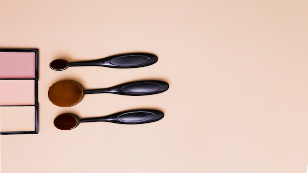 Tavolozza compatta con pennelli trucco ovali su fondo beige