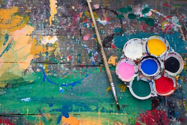 Tavolozza con le spazzole sul fondo di legno della tavola in una vista superiore della composizione