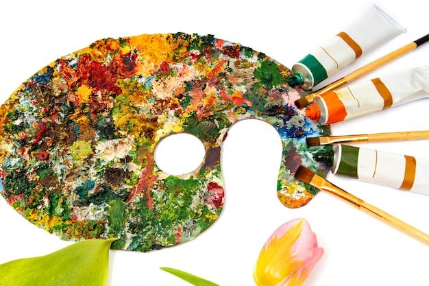 Tavolozza con vernici colorate. gamma di colori variopinta della pittura a olio con una spazzola. pennelli e vernici per il disegno. tulipano su uno sfondo bianco