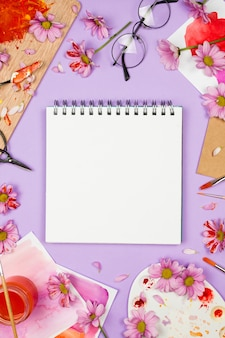 Tavolozza dell'artista con margherite viola, bicchieri, fiori e album da disegno con una pagina vuota