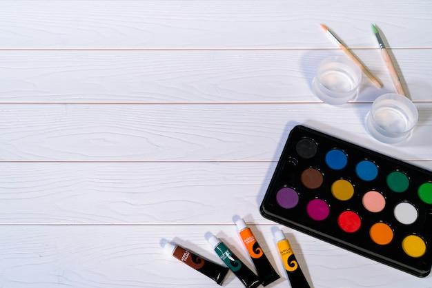 Tavolozza della pittura di colore di acqua sulla tavola di legno bianca