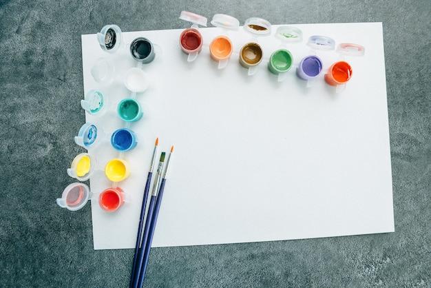 Tavolozza di colori acrilici e pennelli su carta da disegno, vista dall'alto. tema di pittura e arte