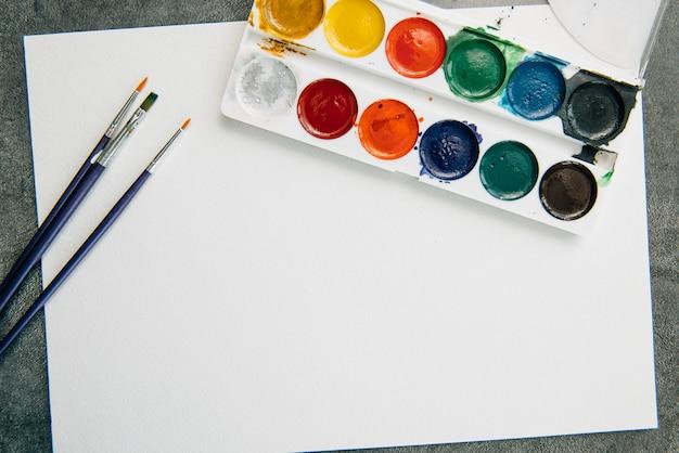 Tavolozza di colori ad acquerello, pennelli e carta per un acquerello, vista dall'alto.