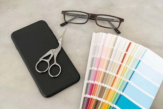 Tavolozza di colori con gli occhiali in posa piatta