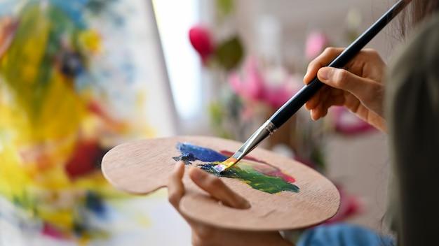 Tavolozza di colori della tenuta della donna dell'artista del primo piano e colore misto per il progetto della pittura acrilica.
