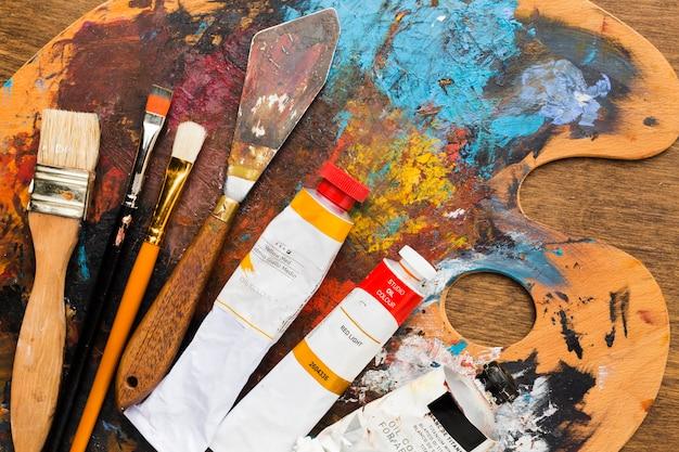 Tavolozza di colori sporchi ad alta vista con pennelli