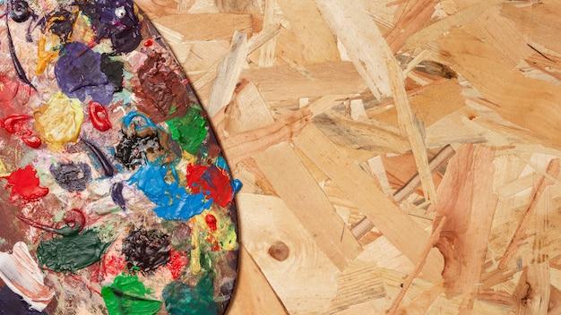 Tavolozza di colori sporchi su sfondo spazio copia in legno