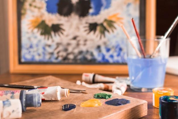 Tavolozza e vernice vicino alla foto incorniciata