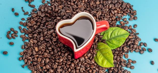 Tazza a forma di cuore con caffè e chicchi di caffè