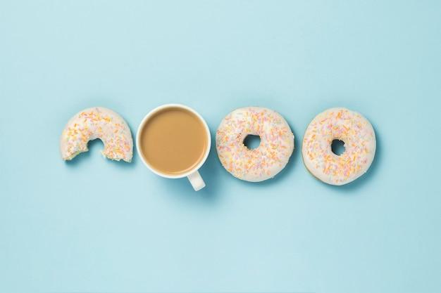 Tazza bianca, caffè o tè al latte e gustose ciambelle fresche su sfondo blu. concetto di panetteria, pasticceria fresca, deliziosa colazione, fast food. vista piana, vista dall'alto.