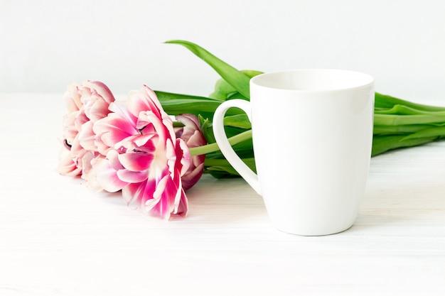 Tazza bianca. chiuda sulla tazza e sui tulipani vuoti