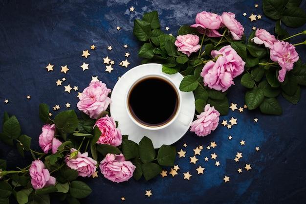 Tazza bianca con caffè nero, stelle e rose rosa su una superficie blu scuro