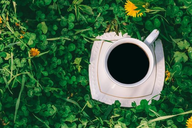 Tazza bianca con caffè nero sul prato con il primo piano verde di vista superiore del trifoglio