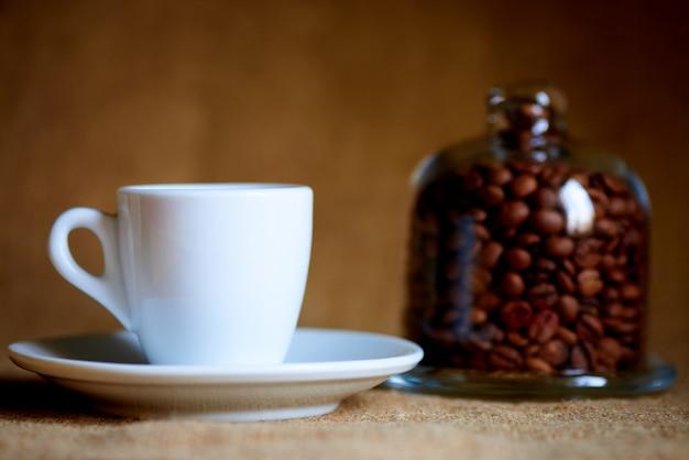 Tazza bianca con caffè su sfocato.