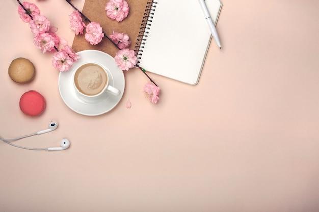 Tazza bianca con cappuccino, fiori di sakura, macarons, taccuino sul rosa