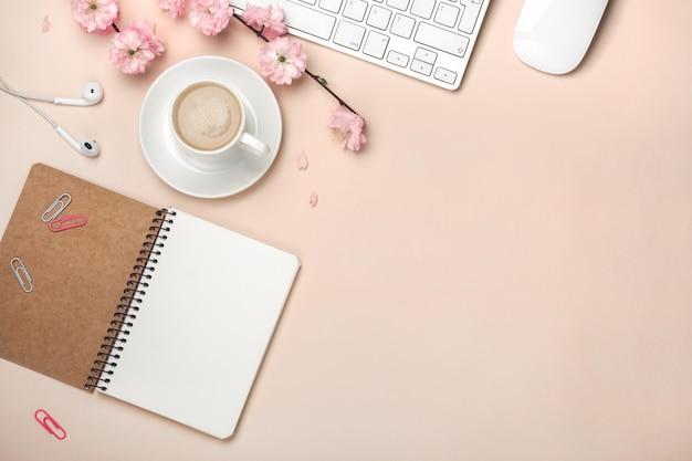Tazza bianca con cappuccino, fiori di sakura, tastiera, sveglia, notebook su uno sfondo rosa pastello