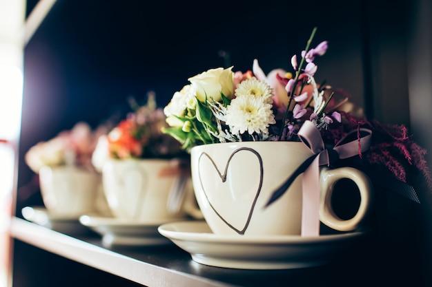 Tazza bianca con fiori sullo scaffale nero. tazza con rose per la festa della mamma. san valentino.