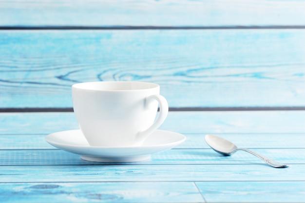 Tazza bianca con piattino e cucchiaino su sfondo blu