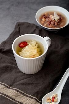 Tazza bianca con tè e una ciotola con zuppa su un panno grigio