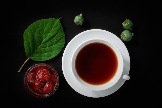 Tazza bianca con tè, marmellata di fragole, scatole di papaveri e foglia di ortensia su uno spazio buio, vista dall'alto, natura morta