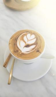 Tazza bianca del caffè del cappuccino o del latte del primo piano con schiuma schiumosa e bastone di cannella sulla tavola bianca.