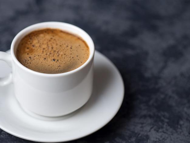Tazza bianca del caffè espresso su superficie scura con copyspace