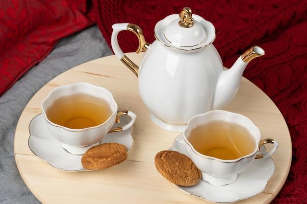 Tazza bianca della porcellana dei biscotti dell'avena e del tè su una tabella