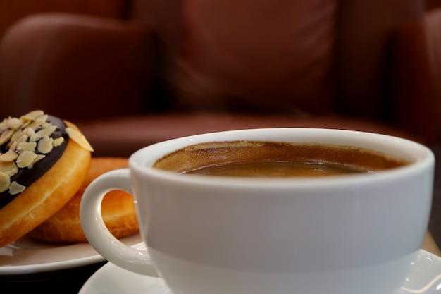 Tazza bianca di caffè caldo con fumo leggero, ciambelle sfocate e poltrona sullo sfondo