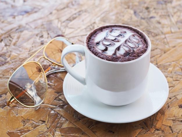 Tazza bianca di cioccolata calda sul tavolo di legno.