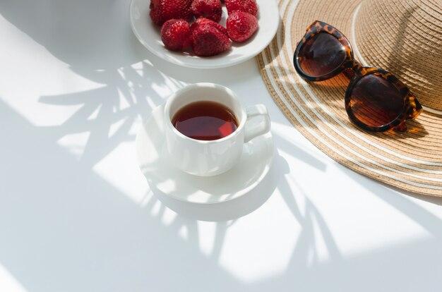 Tazza bianca di tè bianco al mattino con ombra di palma