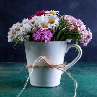 Tazza bianca di vista frontale con fiori colorati in esso