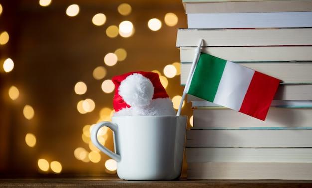 Tazza bianca e cappello di natale con bandiera italia vicino a libri