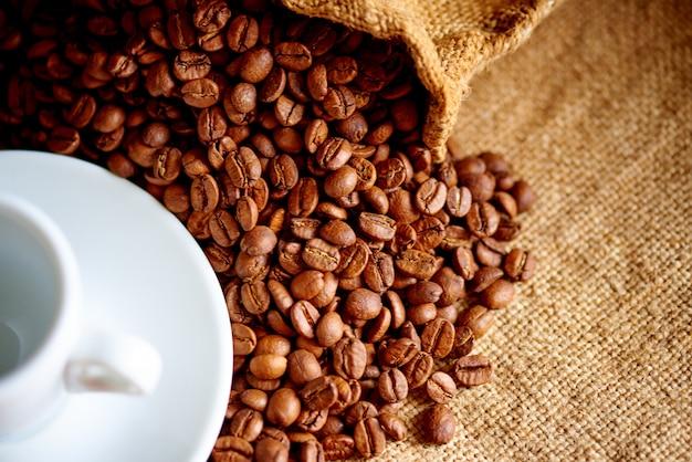 Tazza bianca e chicchi di caffè su tela da imballaggio.