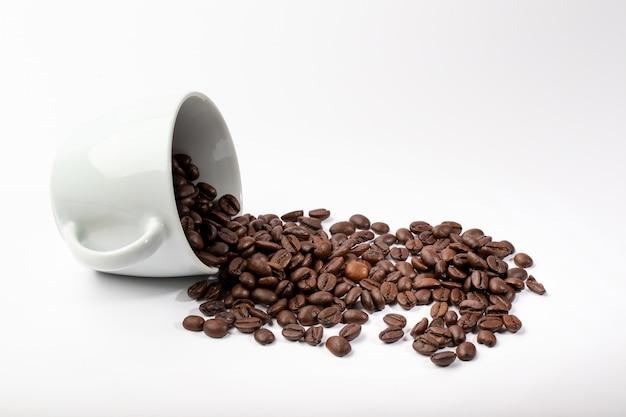 Tazza bianca isolata con i chicchi di caffè