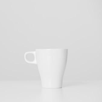 Tazza bianca minimalista del primo piano