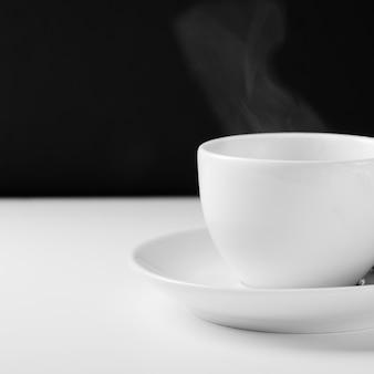 Tazza bianca per il tè con una bevanda calda su una tavola di legno bianca su un fondo nero.