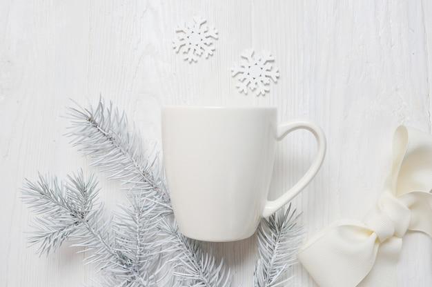 Tazza bianca su un fondo di legno, in decorazioni natalizie.