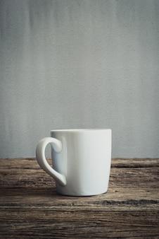 Tazza bianca sul ripiano del tavolo in legno